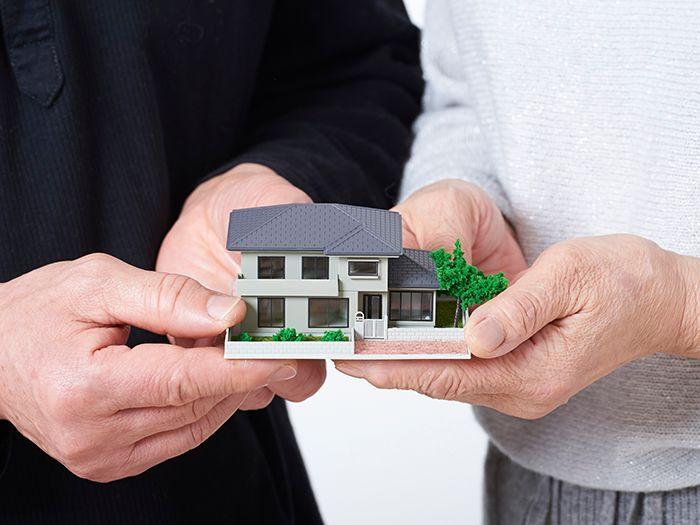 住宅模型を持つ二人の手